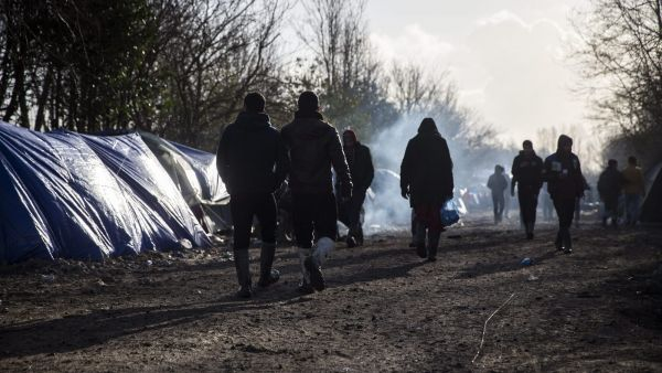 epa05104940 Migrants walk along the shacks and tents of the makeshift migrant camp in Grande-Synthe near Dunkirk, or Dunkerque, France, 16 January 2016. Despite most of the attention is on the so-called 'Jungle' in near-by Calais, the refugee