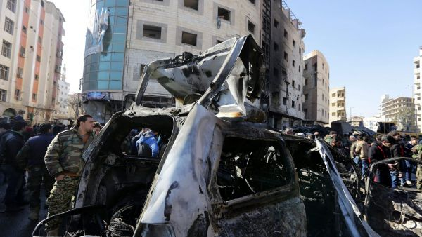epa05137284 Syrians stand next to the wreckage of a vehicle at the site of bombing in the district of al-Sayeda Zainab in southern Damascus, Syria, 31 January 2016. Reports state at least 45 people were killed in three blasts near the Shiite shrine of al