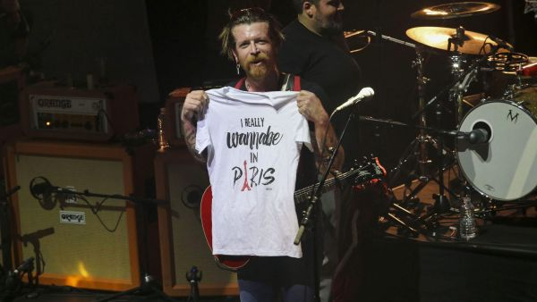 "Frontman of California, USA, rock band Eagles of Death Metal, Jesse Hughes holds a T-shirt with slogan, ""I really wanna'be in Paris"" as the rock band performs Tuesday Feb. 16, 2016, at the Olympia concert hall in Paris, France.  The band"
