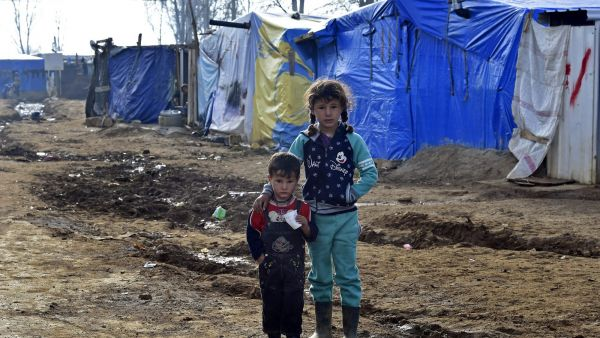 epa05140163 Syrian refugee children stand outside their makeshift shelter at Qab Elias Syrian refugee camp in the Bekaa valley, eastern Lebanon, 02 February 2016. More than 40 thousand Syrian refugees consider Qab Elias camps their primary residence.