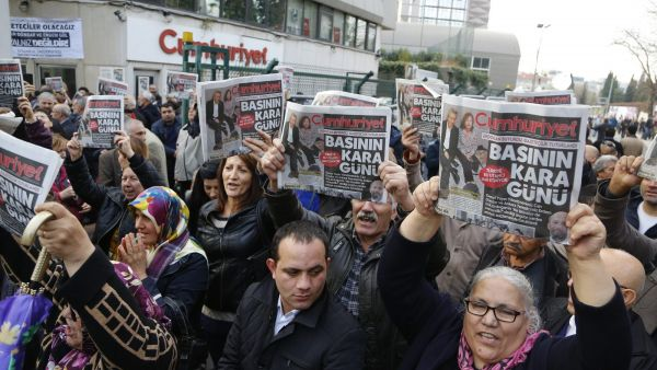 epa05044741 People chant anti-government slogans and hold Cumhuriyet newspaper as they gathered in front Turkish newspaper Cumhuriyet publishing house, in support of Can Dundar and Erdem Gul who were arrested by an Istanbul court in Istanbul, Turkey, 27