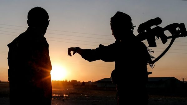 epa04815690 Members of Kurdish People Defence Units (YPG) guard during a sunset near Tel Abyad border gate northern Syria, 23 June 2015. Turkey on 22 June opened the border crossing to Tel Abyad, aka Tell Abiad or Tal Abyad, in northern Syria, allowing