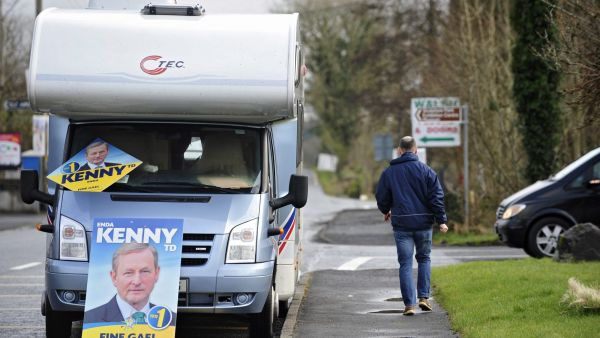 epa05181715 A man walks past a campervan with campaign poster for Fine Gael leader, Irish PM Enda Kenny in Castlebar, County Mayo, Ireland, 26 February 2016. Irish voters go to the polls in the country's general elections.  EPA/AIDAN CRAWLEY