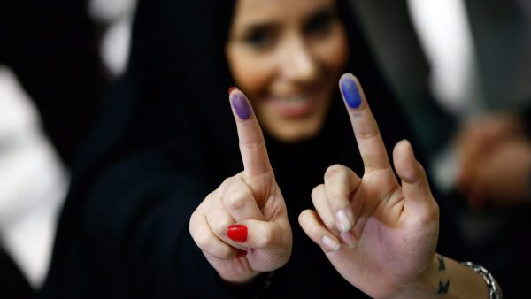 epa05182254 Iranians girls show the ink on their fingers, indicating they have voted, in the parliamentary and Experts Assembly election at a polling station at Ershad Mosque in Tehran, Iran, 26 February 2016. Voting began in Iran's parliamentary