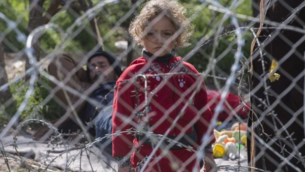 epa05192357 Refugee girl stay behind the fence and wait permission to cross the border between Greece and Macedonia, near Gevgelia, The Former Yugoslav Republic of Macedonia, 03 March 2016. Migration restrictions along the so-called Balkan route, the main