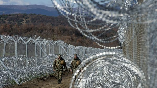epa05193704 Macedonian soldiers patrol between the fences at the border line between Greece and Macedonia, near Gevgelija, The Former Yugoslav Republic of Macedonia, 04 March 2016. Migration restrictions along the so-called Balkan route, the main corridor