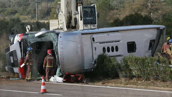 epa05222051 Emergency services' members work at the site of a coach crash that has left at least 14 students dead at the AP-7 motorway in Freginals, in the province of Tarragona, northeastern Spain, 20 March 2016. The coach carrying dozens of Erasmus