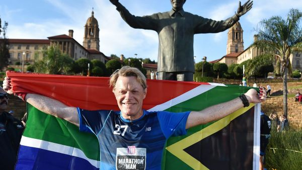 British comedian Eddie Izzard holds a South African flag beneath a statue of former president Nelson Mandela at the government's Union Buildings in Pretoria, South Africa, Sunday, March 20, 2016. Izzard has completed his challenge to run 27 marathons