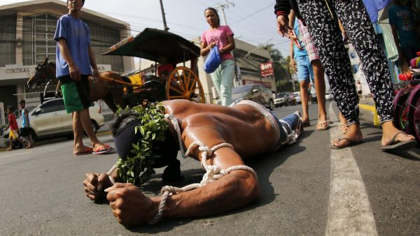 epa05228405 A Filipino flagellant crawls along a street on Maundy Thursday, in San Fernando city, Pampanga Province, north of Manila, Philippines, 24 March 2016. Many Filipino Catholic penitents mark the Holy Week by submitting to different forms of