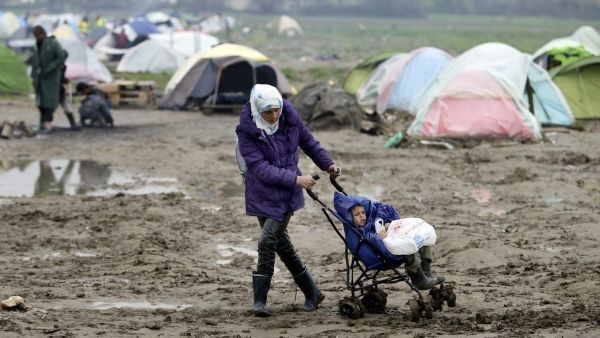 epa05227428 A migrant tries to push a pram through mud at the refugee camp on the Greek-Macedonian border in Idomeni, Greece, 23 March 2016. Migration restrictions along the so-called Balkan route, the main path for migrants and refugees from the Middle