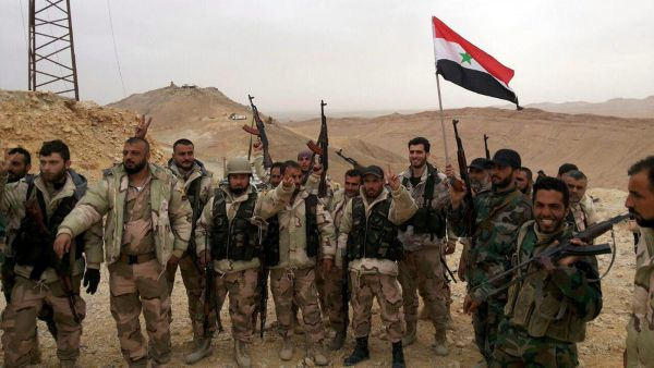epa05231923 A handout photo made available by the official Syrian Arab News Agency (SANA) shows Syrian government soldiers holding the national flag and posing during an operation in Palmyra, central Homs province, Syria, 26 March 2016. According to SANA,