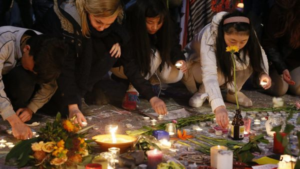 epa05229728 People gather and pay tribute to the many people killed and injured in multiple terrorist attacks accross Brussels on 22 March, at Place de la Bourse,  in Brussels, Belgium, 24 March 2016. At least 31 people were killed with hundreds injured