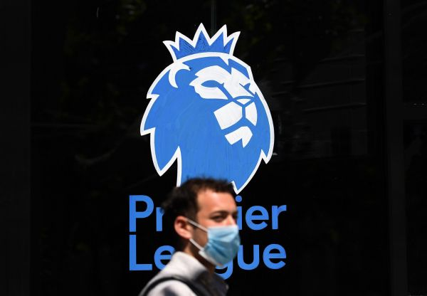 epa08452372 A man wearing a protective mask walks past the Premier League logo in London, Britain, 29 May, 2020. Premier League football is set to return after some twelve weeks of lockdown, with top-flight games in England scheduled to resume June 17. Countries around the world are taking increased measures to stem the widespread of the SARS-CoV-2 coronavirus which causes the Covid-19 disease.  EPA-EFE/ANDY RAIN