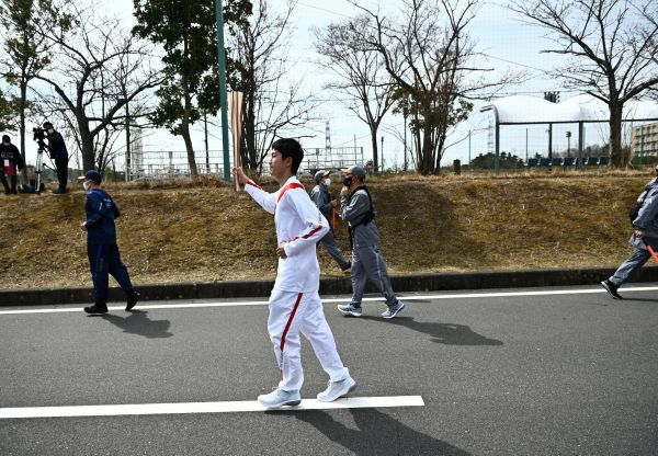 epa09095226 Japanese high school student Asato Owada carries the Olympic Torch during the torch relay grand start outside J-Village National Training Centre in Naraha, Fukushima Prefecture, Japan, 25 March 2021. The postponed Tokyo 2020 Olympic Games are scheduled to start on 23 July 2021 and some 10,000 torchbearers will run across the country along a 121-day journey.  EPA-EFE/PHILIP FONG / POOL
