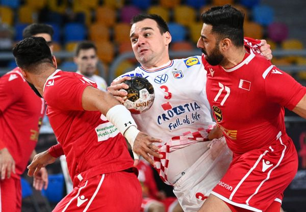 epa08956185 Croatia's Marino Maric (C) in action against Bahrain's Jasim Alsalatna (R) during the match between Croatia and Bahrain at the 27th Men's Handball World Championship in Cairo, Egypt, 21 January 2021.  EPA-EFE/Anne-Christine Poujoulat / POOL