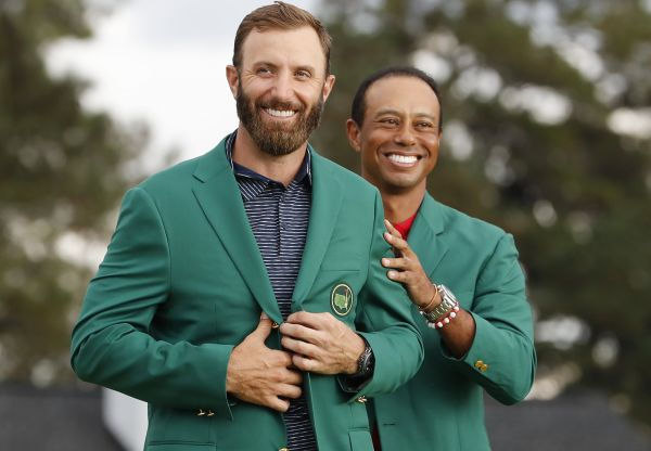 epa08822881 Dustin Johnson of the US (L) is presented his green jacket by defending champion Tiger Woods of the US (R) after Johnson won the 2020 Masters Tournament at the Augusta National Golf Club in Augusta, Georgia, USA, 15 November 2020. After being delayed seven months by the coronavirus pandemic, the 2020 Masters Tournament is being held without patrons 12 November through 15 November.  EPA-EFE/ERIK S. LESSER